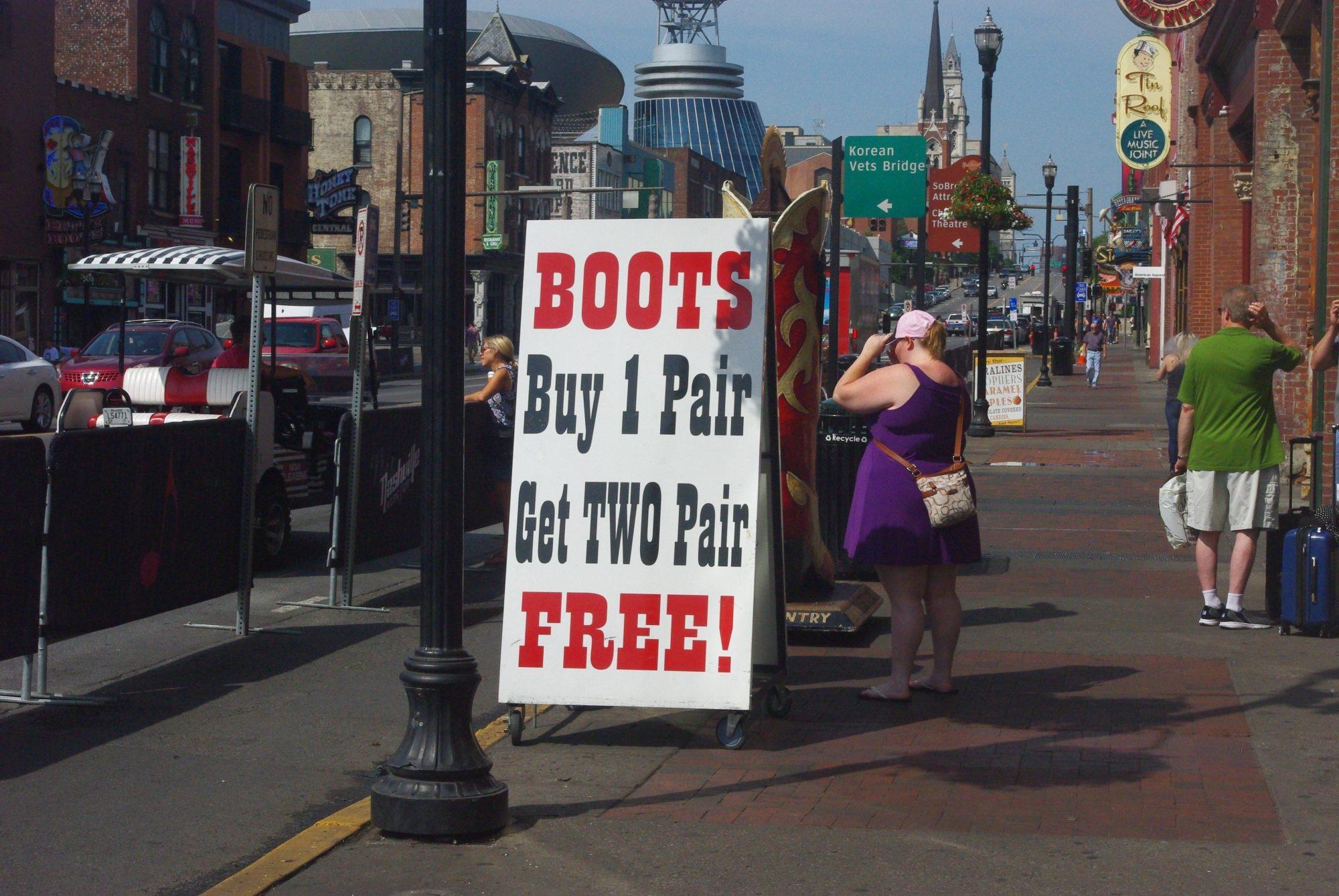 """Broadway. Un commerce sur 2 vend des bottes et des chapeaux et l'autre est un bar (""""honky tonk"""")"""